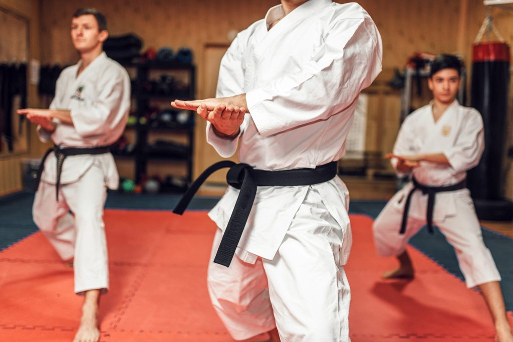 Martial arts karate master and his disciples in white uniform and black belts, fight training in action, workout in gym